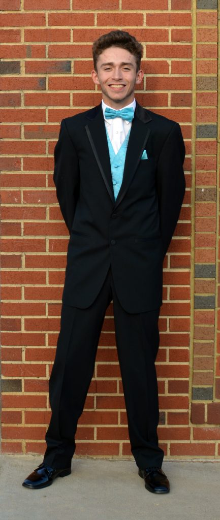 A young man in a black tuxedo with a light blue vest and tie stands in front of a brick wall.