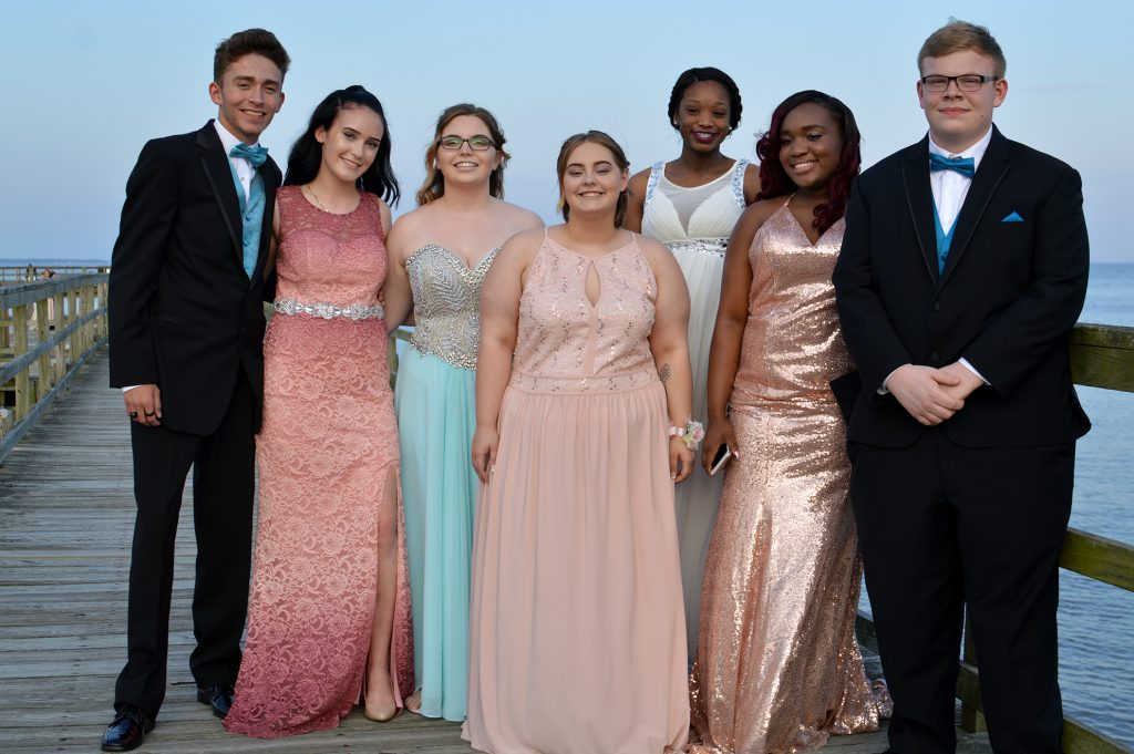 A mixed group of young men, women, and races on prom night. The group is standing in formal dress on a pier.