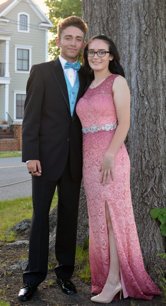 A young couple, man in black tux, woman in a pink and purple dress, stand in front of  a tree