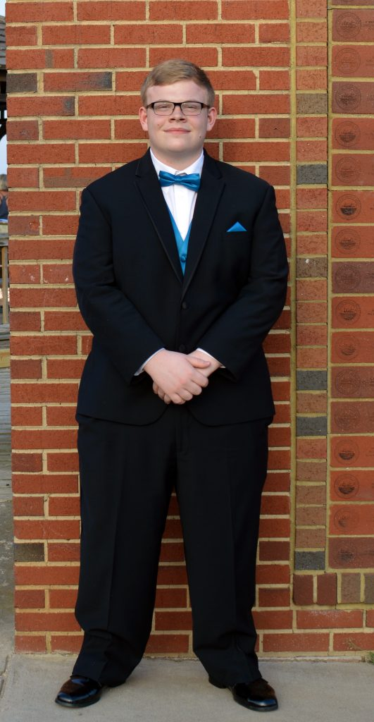 A young man in a black tuxedo with a royal blue bow tie and vest stands in front of a brick wall