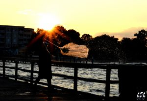 A man pulls a net out of the water as the sunsets in the distance