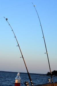 Two fishing poles grace the sky on a pier in front of beautiful water