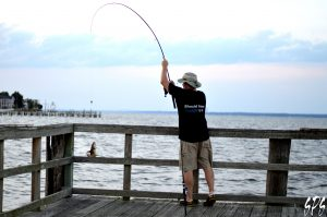 A man in shorts catches a fish on a pier