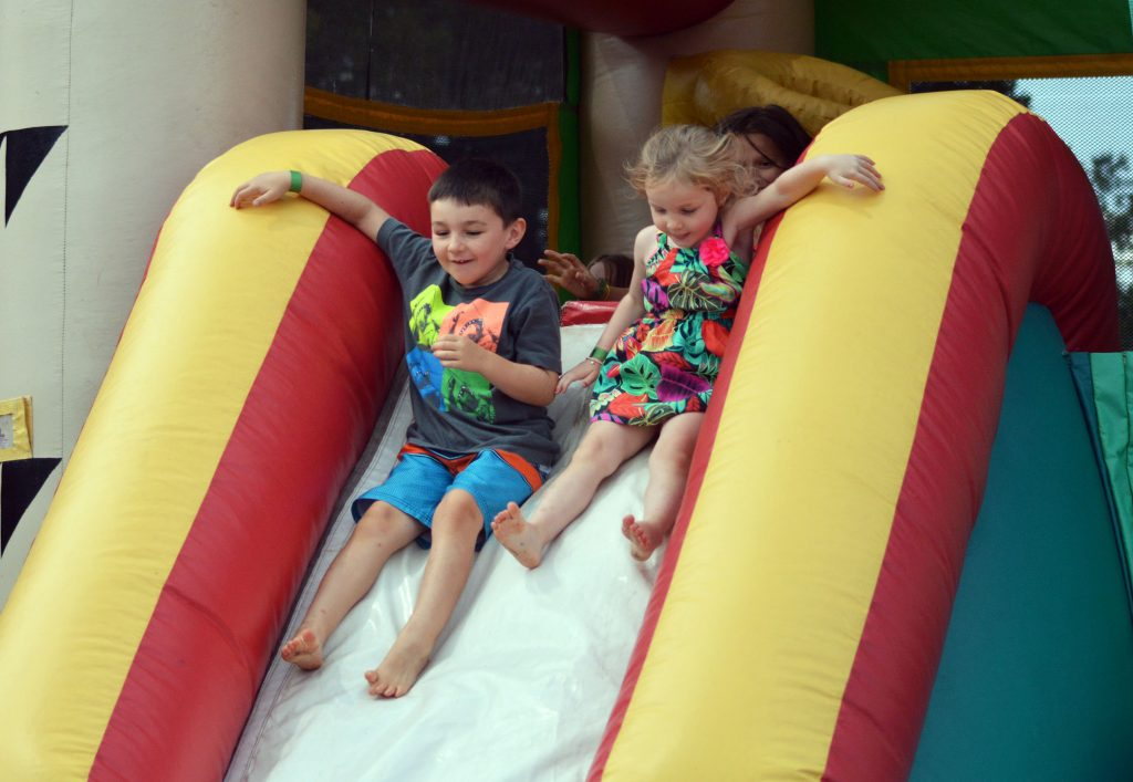 Two children slide down a white, red and yellow water slide.