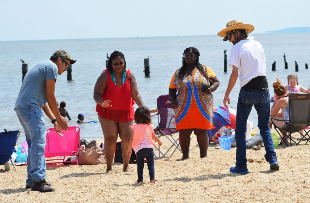 Two black women, twho white men, and a small black child dance to the beat on the beach